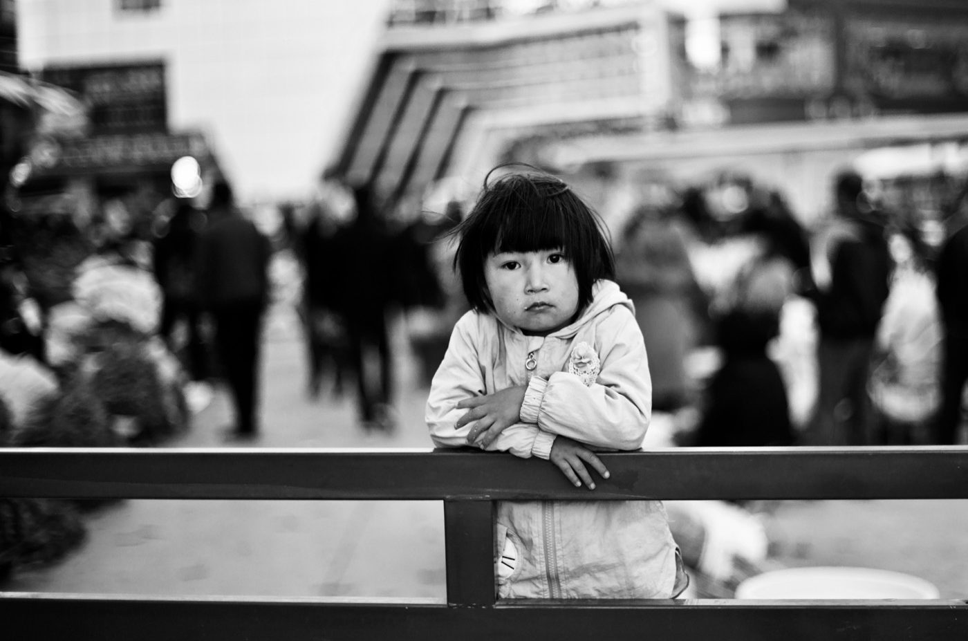 A young girl waits while her father works, Kunming flower market.