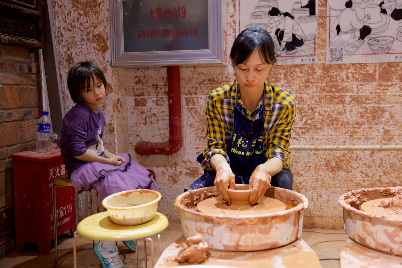 Lily tries her hand at making the local purple pot.  Jianshui, China