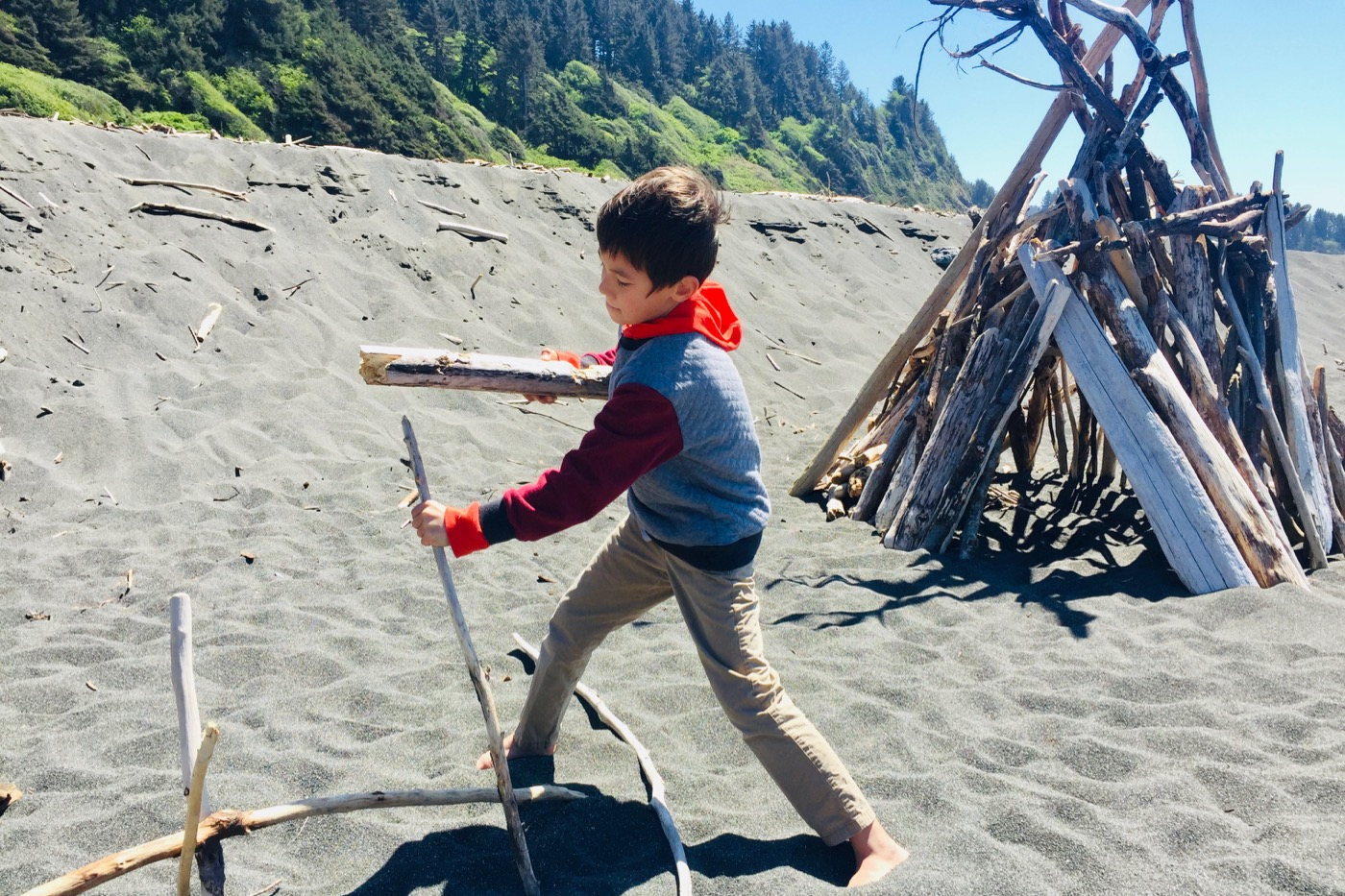 Kai building a teepee on the California coast.